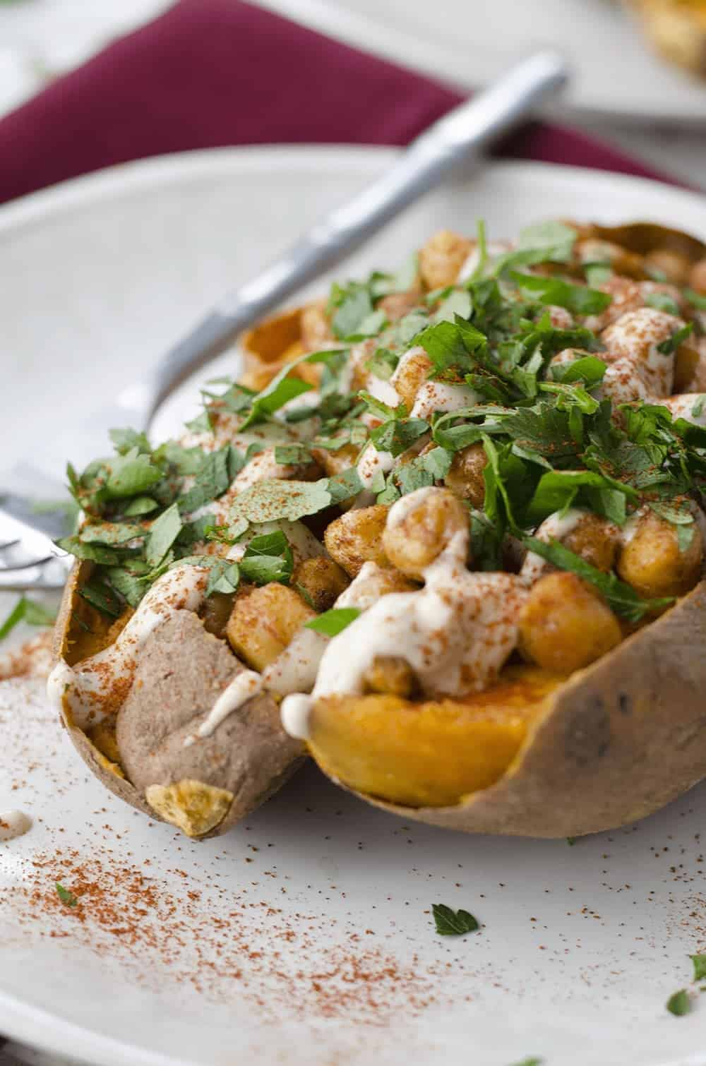 Vegan stuffed sweet potatoes! Roasted sweet potatoes stuffed with spiced chickpeas, garlic tahini sauce and fresh herbs. Gluten-free. | www.delishknowledge.com