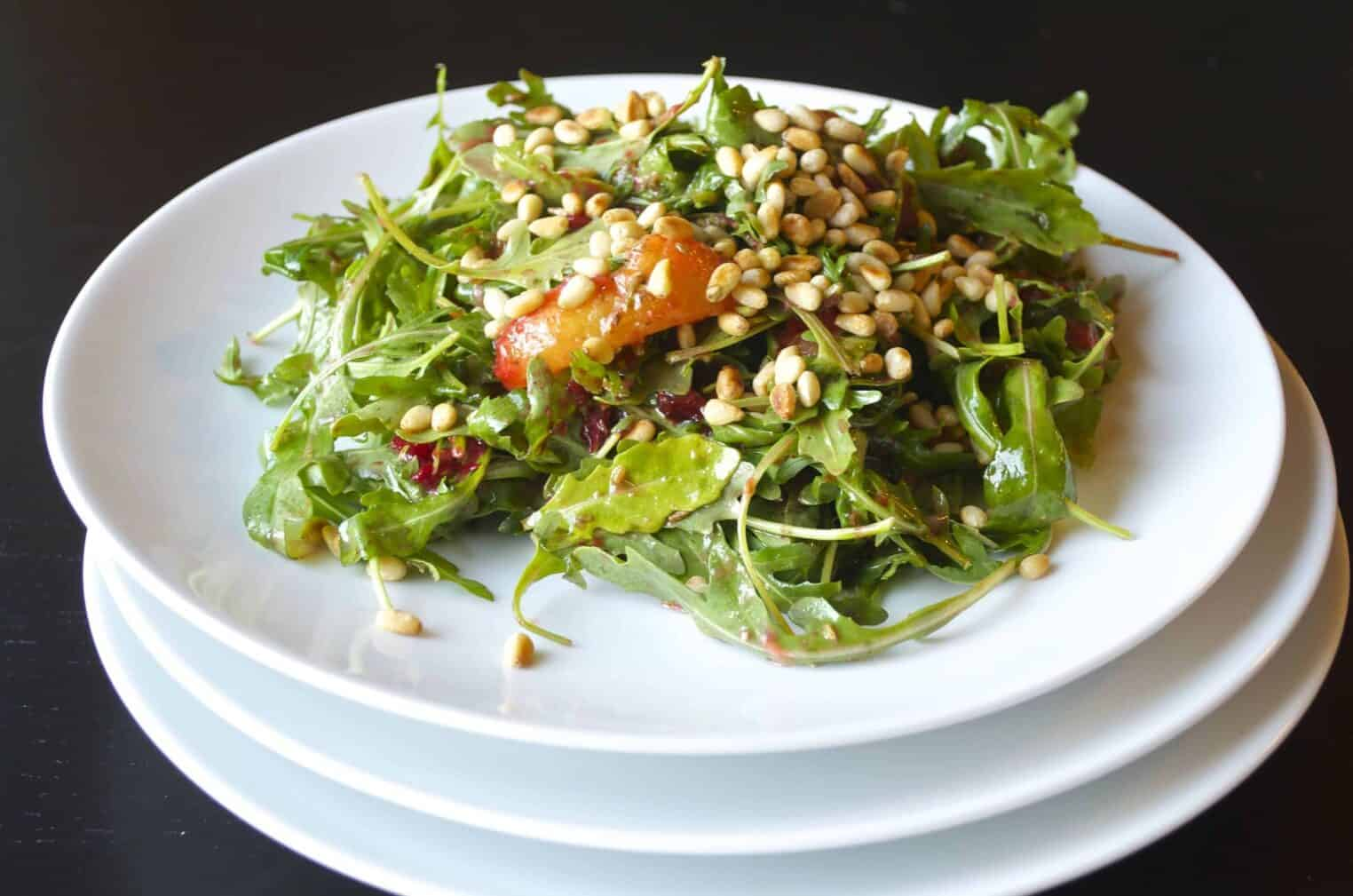 A healthy recipe of grilled plum and arugula salad with toasted pine nuts. Vegan and gluten-free.