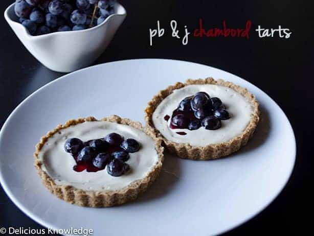 Raw, vegan and gluten free peanut butter and jelly tarts. Crust filled with raw peanut butter cheesecake filling and topped with chambord soaked grapes.