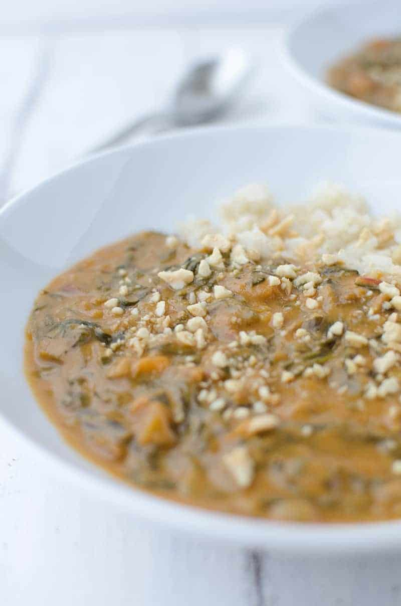 Traditional African peanut soup in a white bowl with brown rice