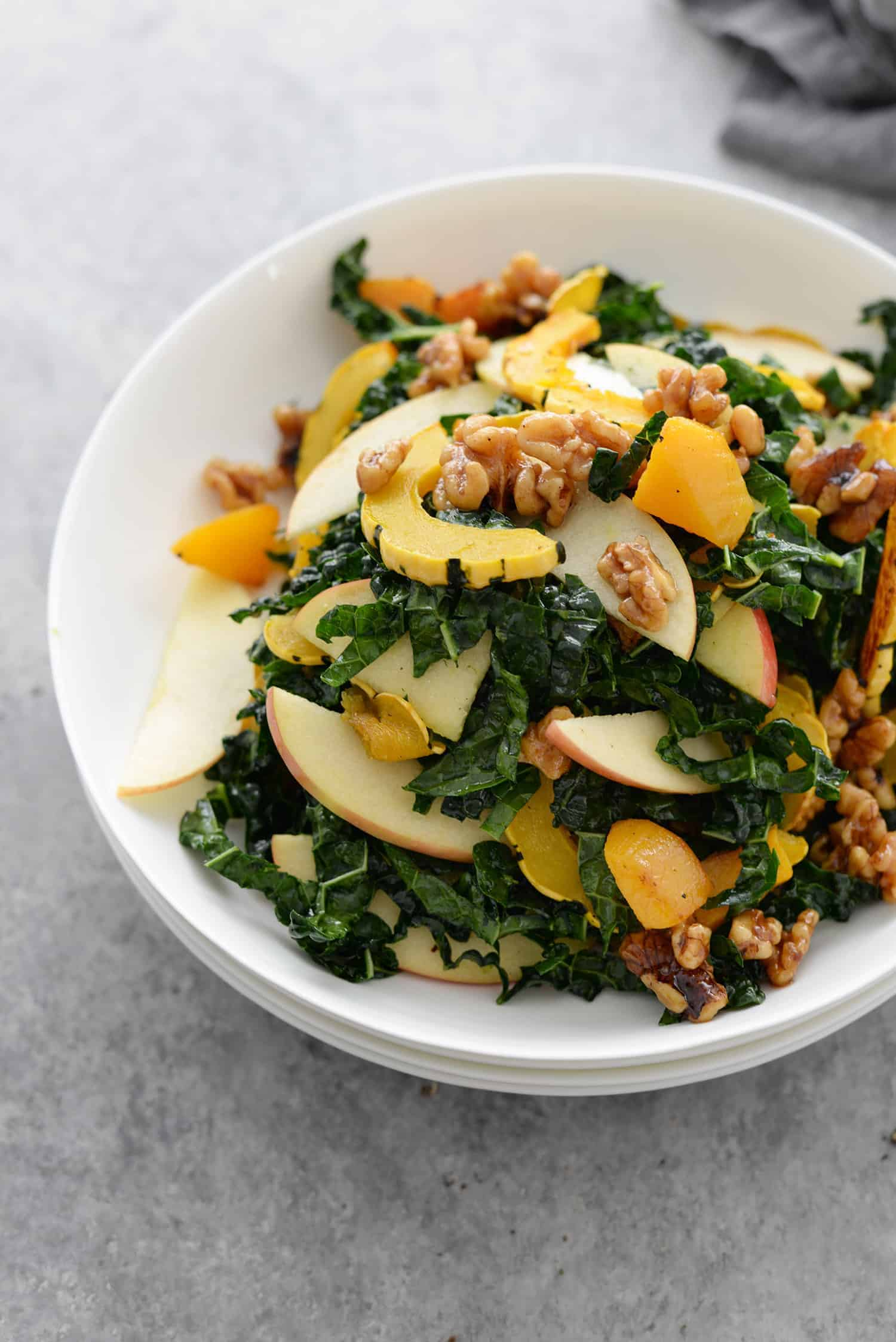 Autumn Squash, Kale and Apple Salad. You've gotta try this Thanksgiving or Holiday salad! Kale, roasted squash, apple and candied walnuts in a maple-cinnamon dressing. #vegan and #glutenfree | www.delishknowledge.com