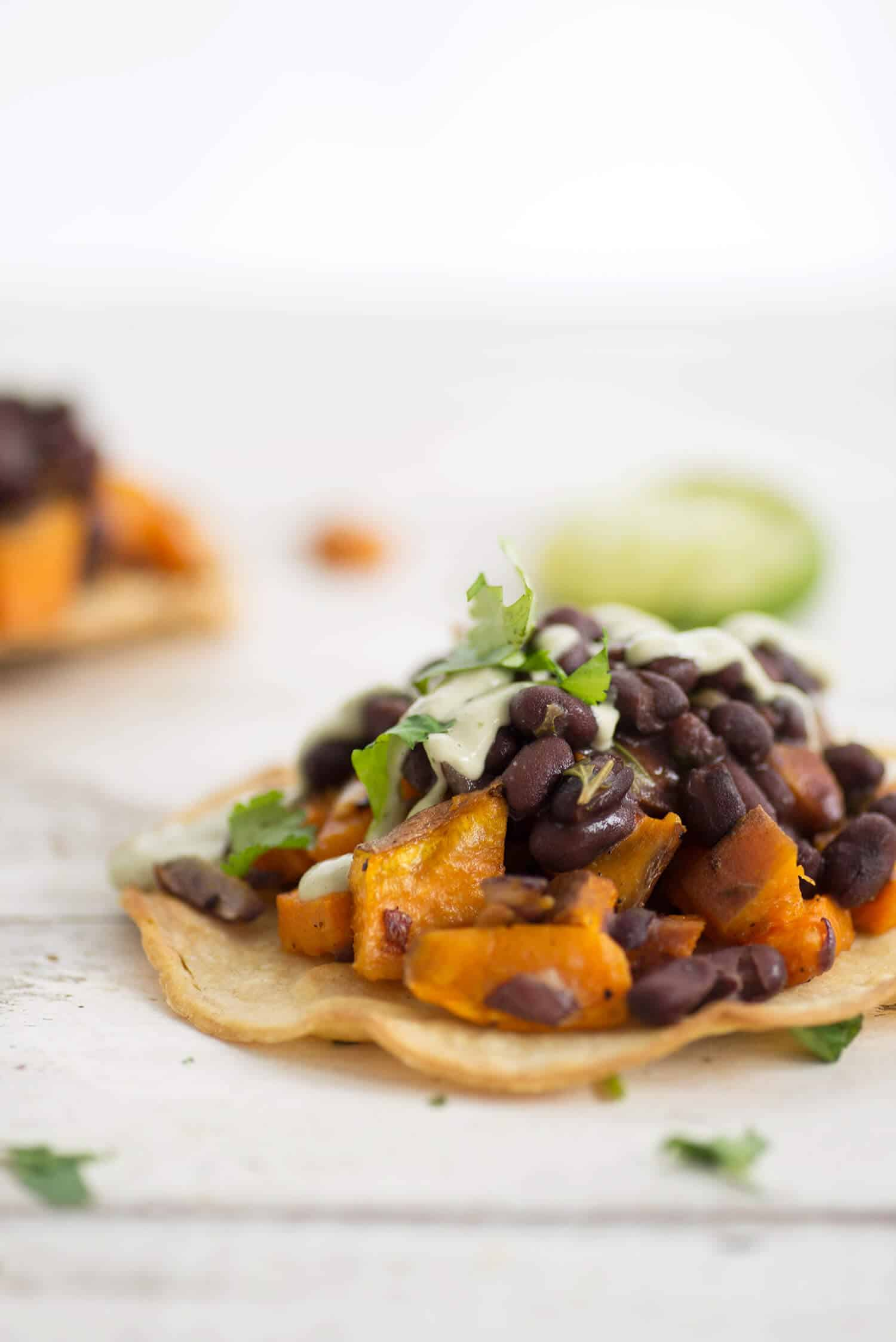 Black Bean and Sweet Potato Tostadas! Seasoned black beans piled high with roasted sweet potatoes, covered with avocado creme. Vegan & GlutenFree | www.delishknowledge.com