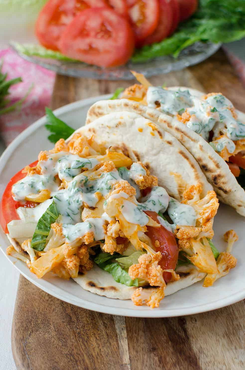 Buffalo Cauliflower Flatbreads! These vegan sandwiches are packed with so much flavor! Roasted buffalo cauliflower on homemade flatbreads. Topped with a simple dairy-free ranch dressing.   www.delishknowledge.com