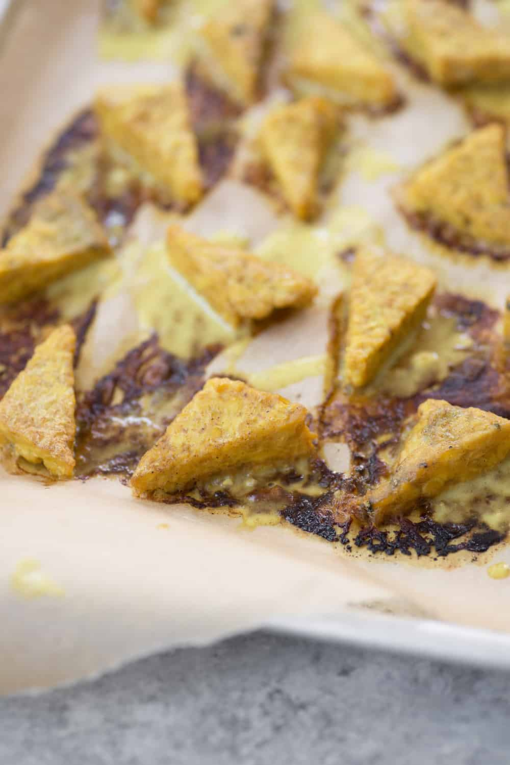 curry tempeh triangles on a baking sheet