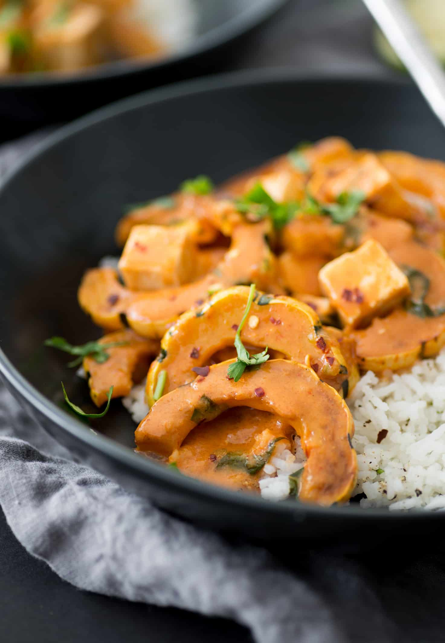 Vegan Delicata Squash Red Curry! If you're looking for a healthy, plant-based dinner- this is it! Simmered tofu and squash in a mild red curry sauce. Easily gluten-free.   www.delishknowledge.com
