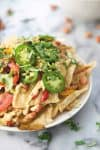 Fajita Vegan Nachos! The ultimate plant-based nachos. Tortillas, chewy taco tofu, seasoned peppers, homemade cheese sauce, pinto beans and more! Gluten-free. | www.delishknowledge.com
