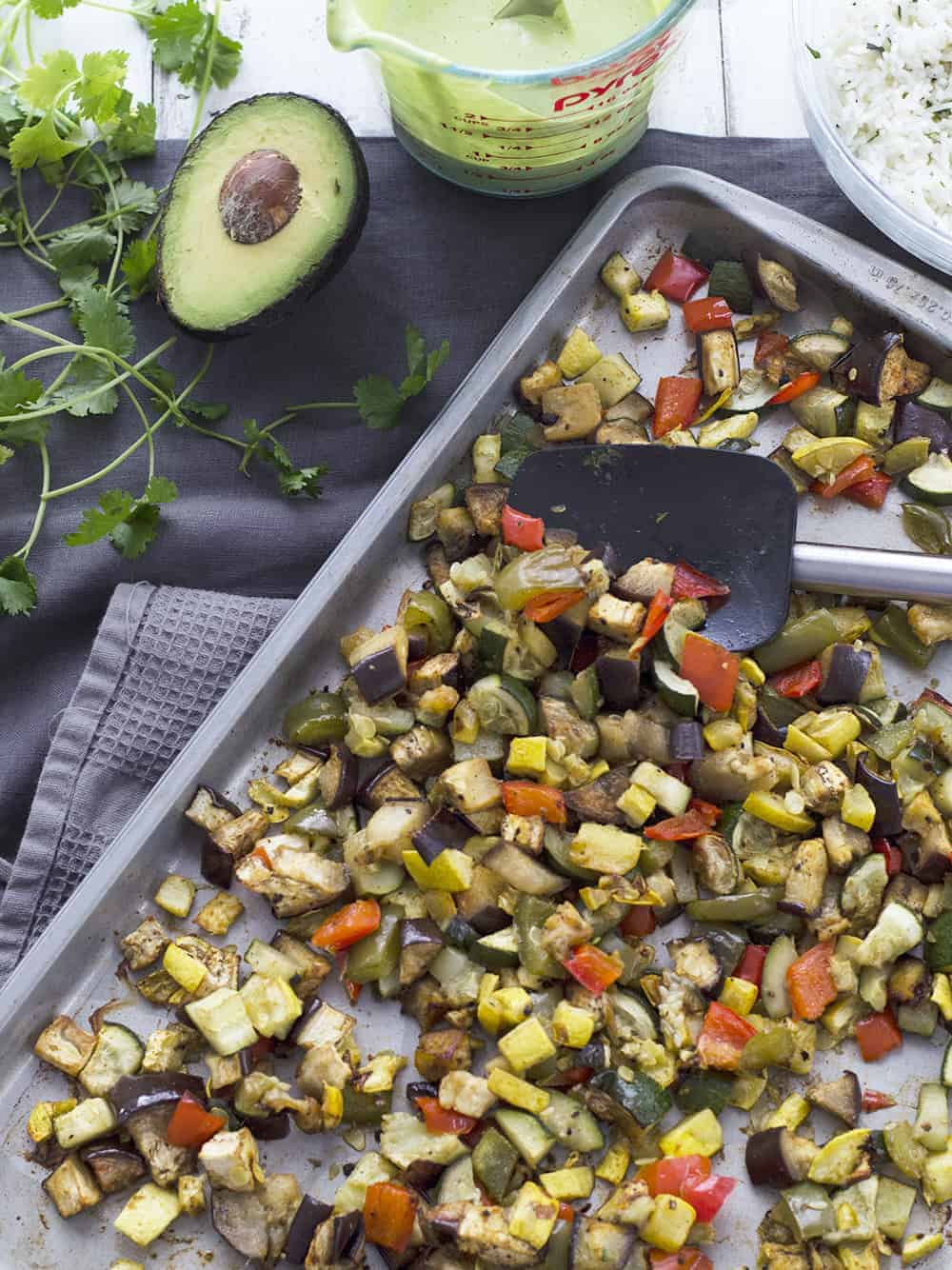 Vegetable Fajita Bowls with Creamy Cilantro Sauce! Roasted summer vegetables, cilantro rice, avocado and a creamy, dairy-free cilantro sauce. Vegan and Glutenfree | www.delishknowledge.com