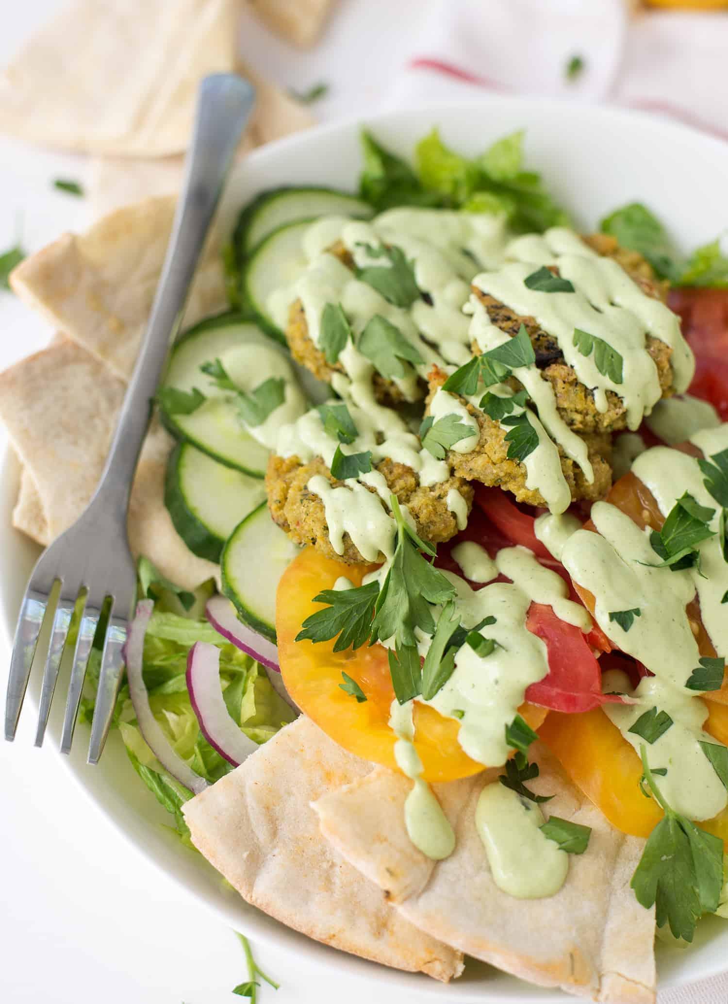 Falafel Salad with Tahini Parsley dressing! Crispy vegan falafel patties on top of salad with tahini parsley dressing.   www.delishknowledge.com
