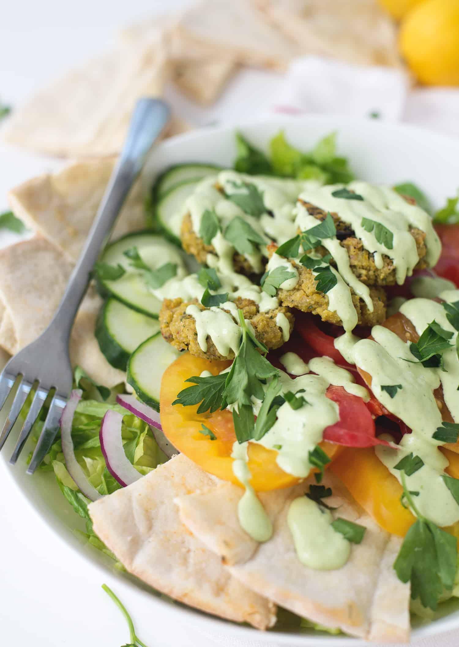 Falafel Salad with Tahini Parsley dressing! Crispy vegan falafel patties on top of salad with tahini parsley dressing. | www.delishknowledge.com