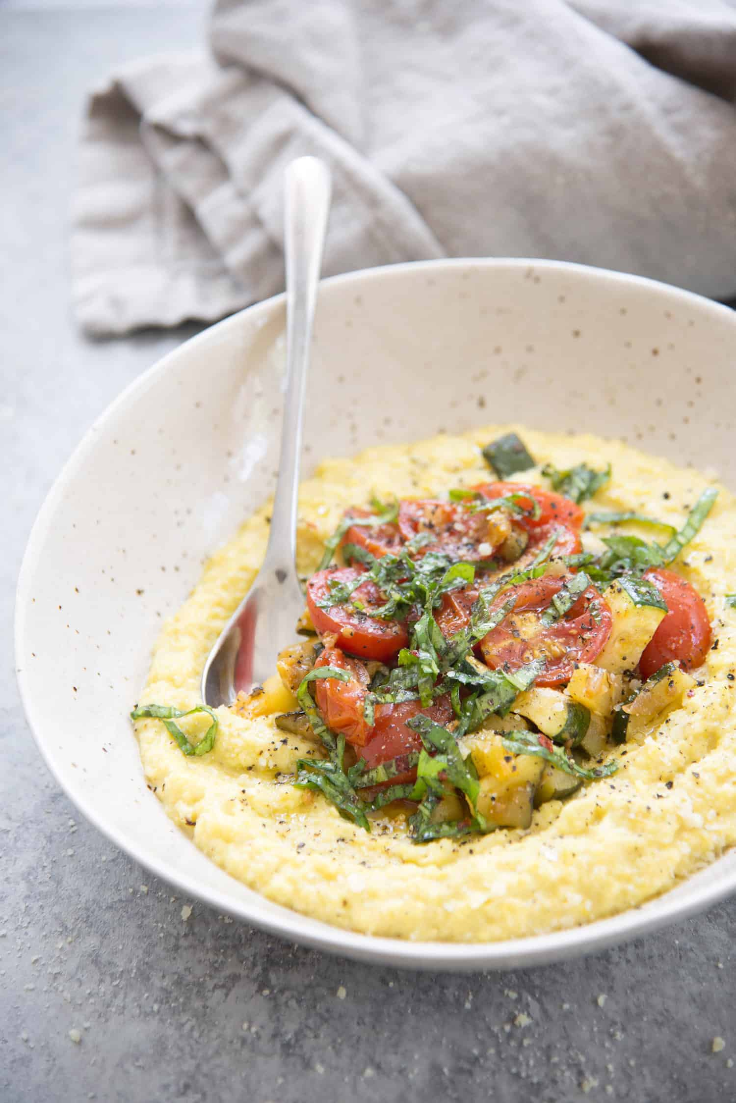 Fresh Corn Polenta with Farm Vegetables and Spicy Basil Oil. The vegan and gluten-free dinner is perfect for summer! Make the most of farmer's market produce; fresh corn polenta topped with sauteed farm vegetables and a drizzle of spicy basil oil. | www.delishknowledge.com