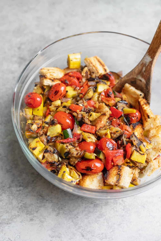 close up shot of grilled panzanella salad with basil dressing