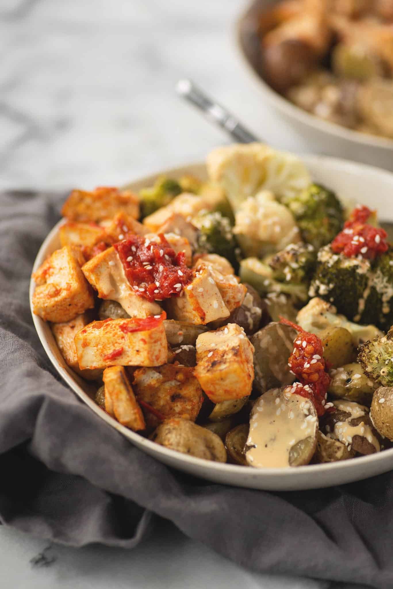 Harissa Tahini Tofu Buddha Bowls! Harissa roasted tofu, roasted potatoes, broccoli and cauliflower covered in a tahini harissa dressing. Grain-free, vegan and gluten-free. | www.delishknowledge.com