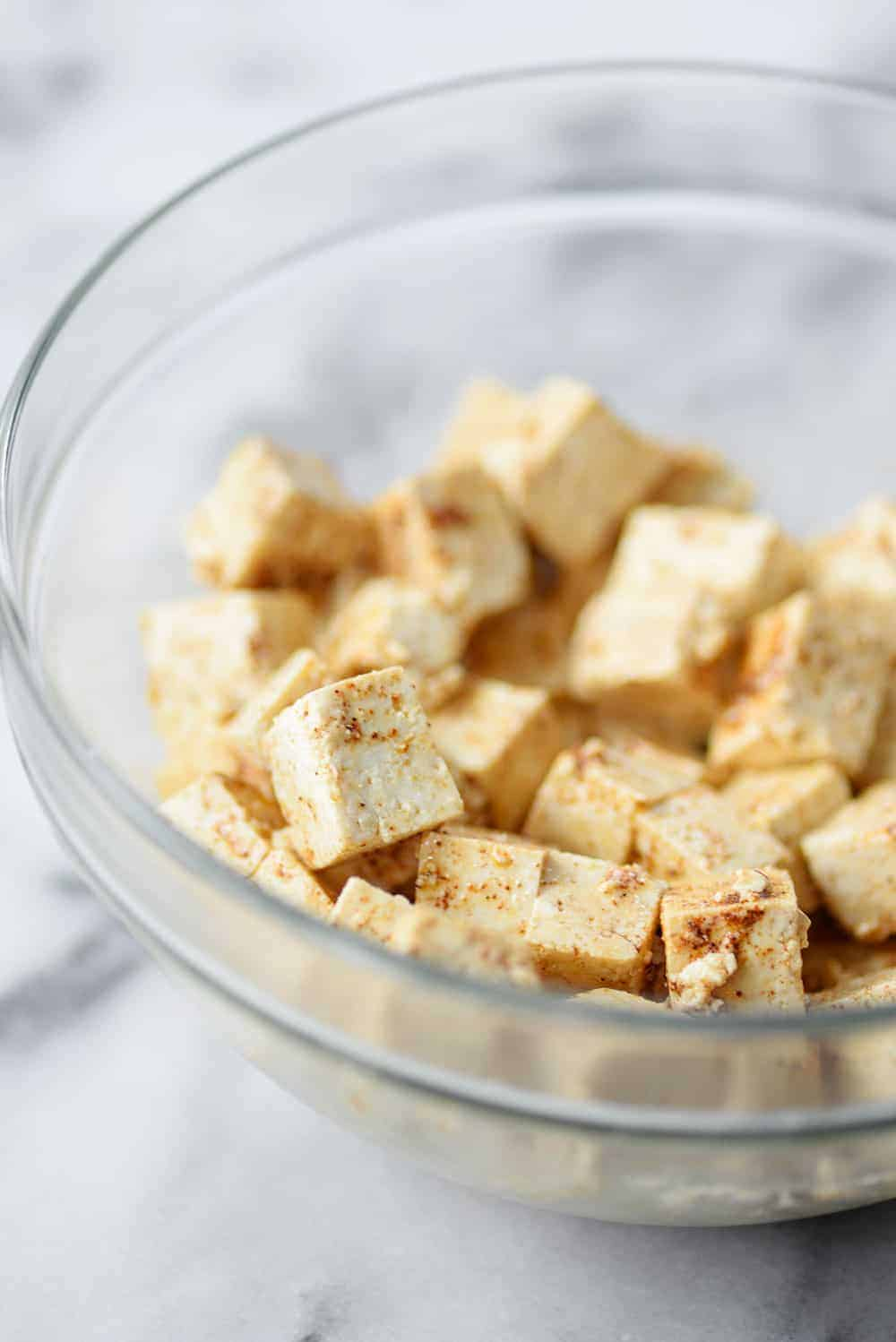 tofu tossed with seasonings in a bowl