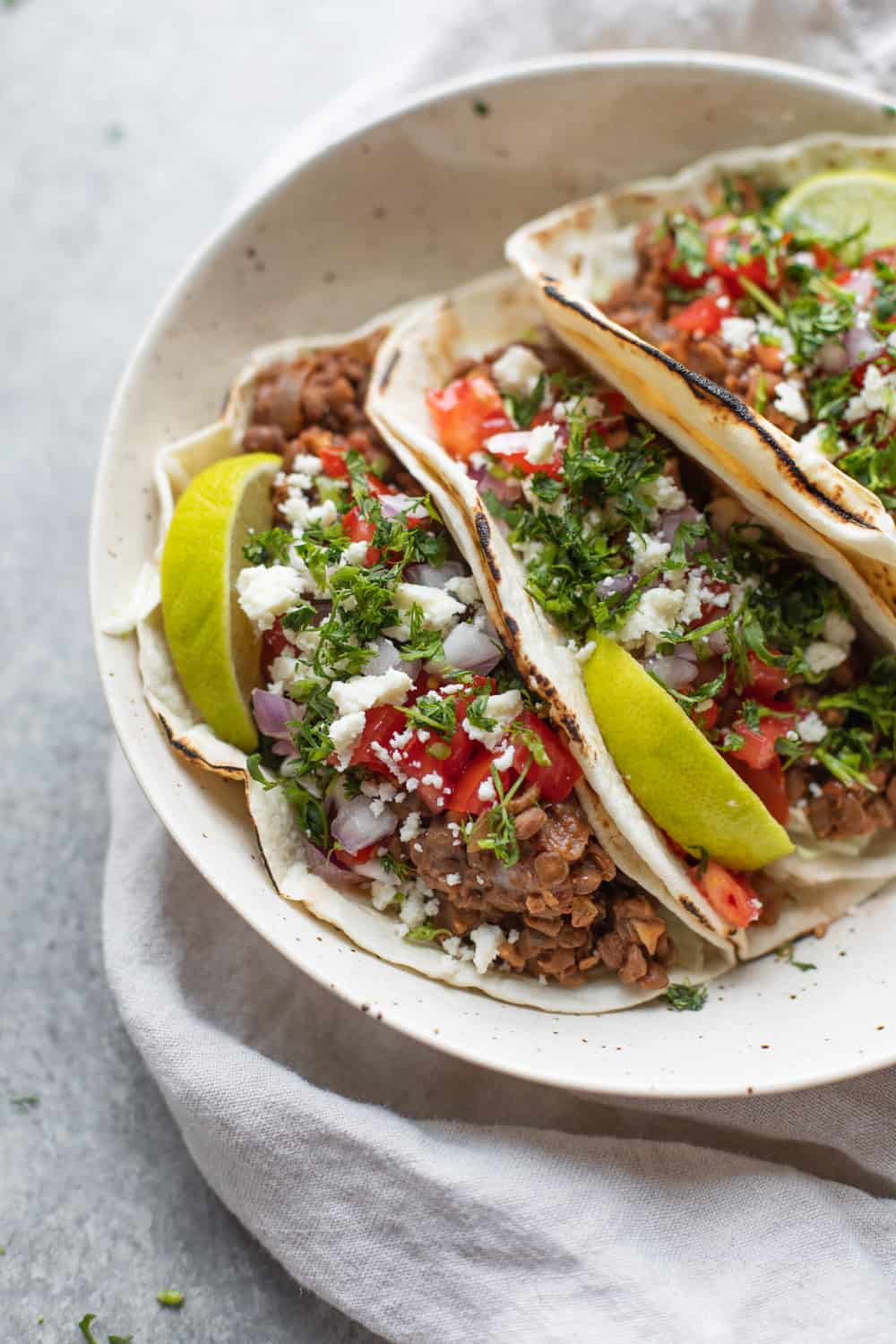 three tacos with lime