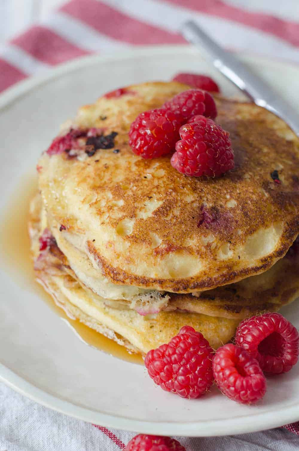 Lemon Raspberry Pancakes, perfect for Valentines Day brunch! Soft and fluffy pancakes infused with lemon zest and frozen raspberries. | www.delishknowledge.com