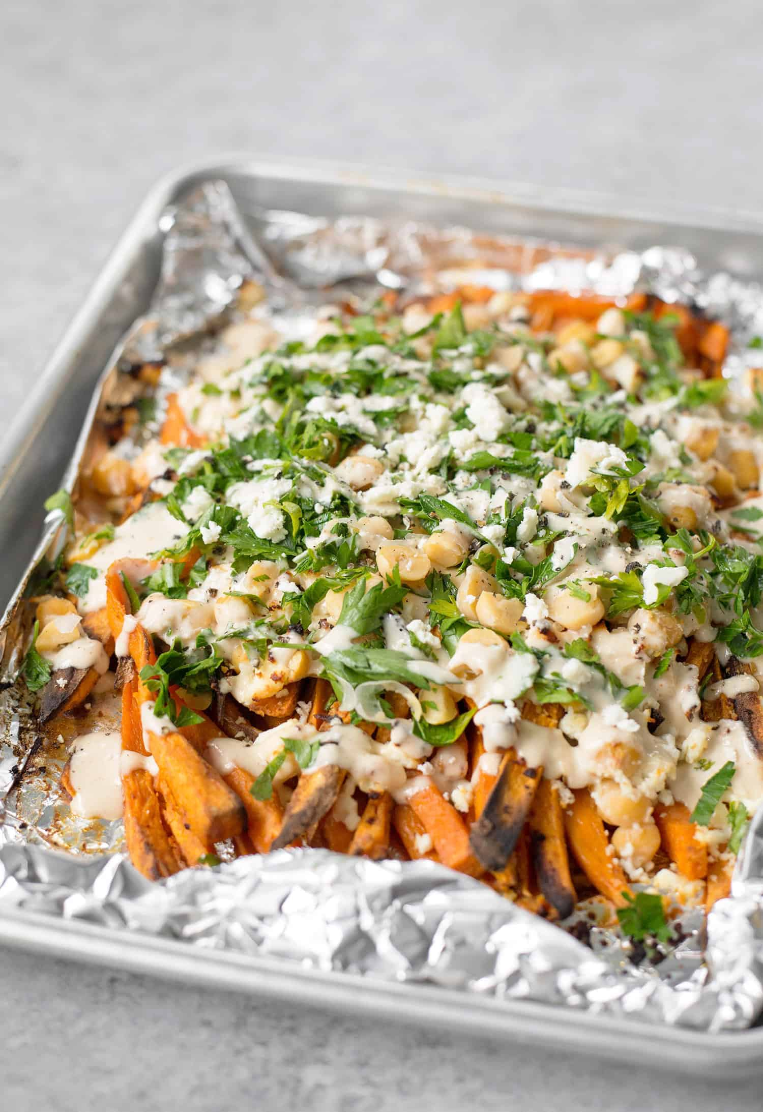 Loaded Sweet Potato Greek Fries! Crispy sweet potato fries with feta, chickpeas, parsley and a lemon-tahini sauce. Vegetarian and gluten-free | www.delishknowledge.com
