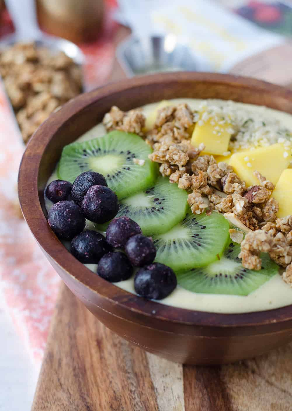 Tropical Mango Smoothie Bowl! A delicious, protein packet breakfast topped with THE BEST homemade granola. | www.delishknowledge.com