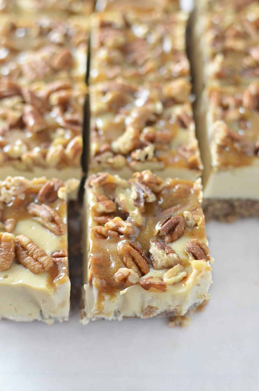 Pecan Pie Cheesecake Bars! Vegan and Gluten-Free! You are going to love these clean eating bars! Pecan Pie crust with dairy-free, no bake cheesecake filling. Topped with toasted pecans and maple-caramel syrup. A must make for Thanksgiving, Christmas or the Holidays! | www.delishknowledge.com