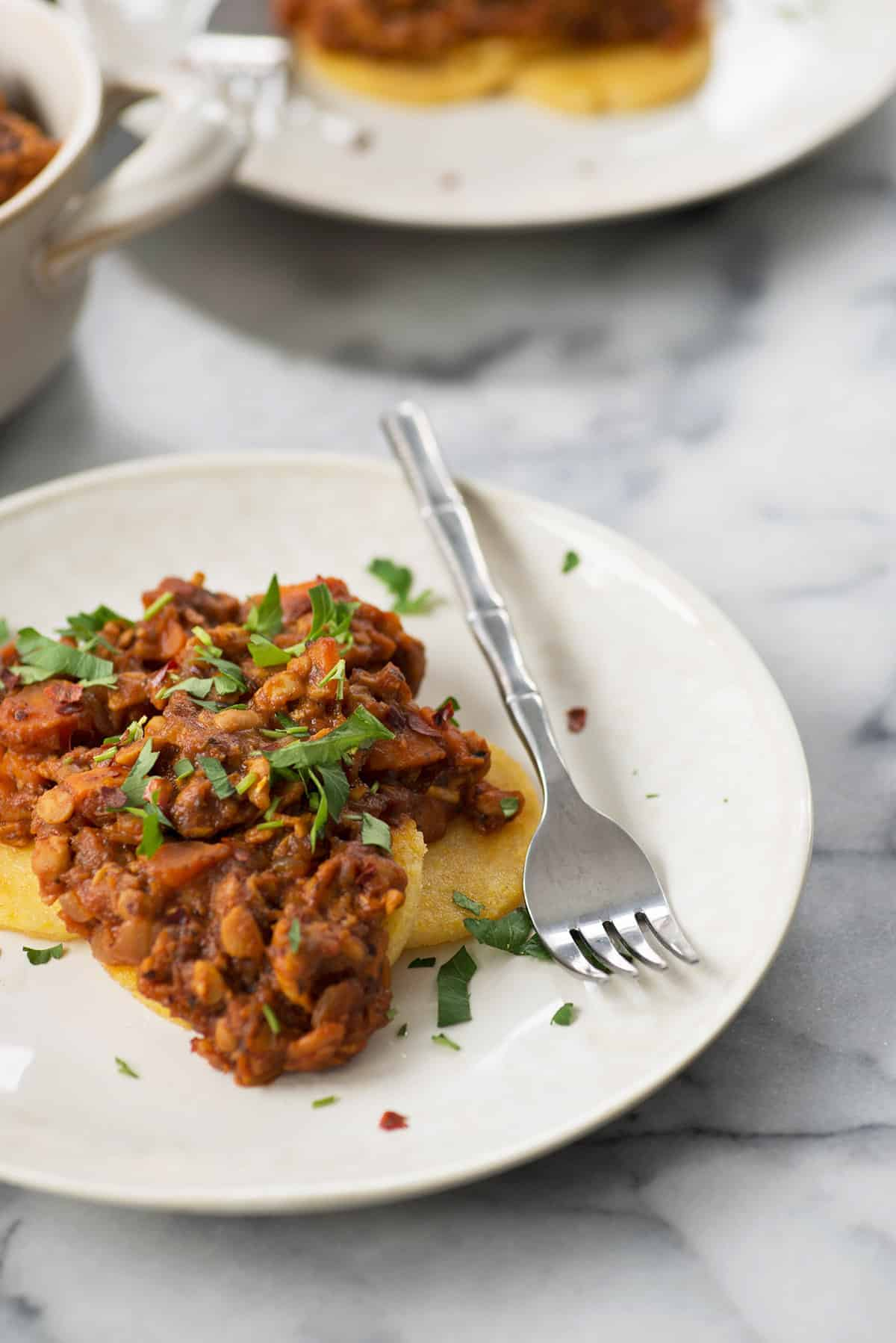 Polenta Cakes with Tempeh Bolognese! Crispy polenta topped with a meaty, vegan ragu. Healthy comfort food! | www.delishknowledge.com