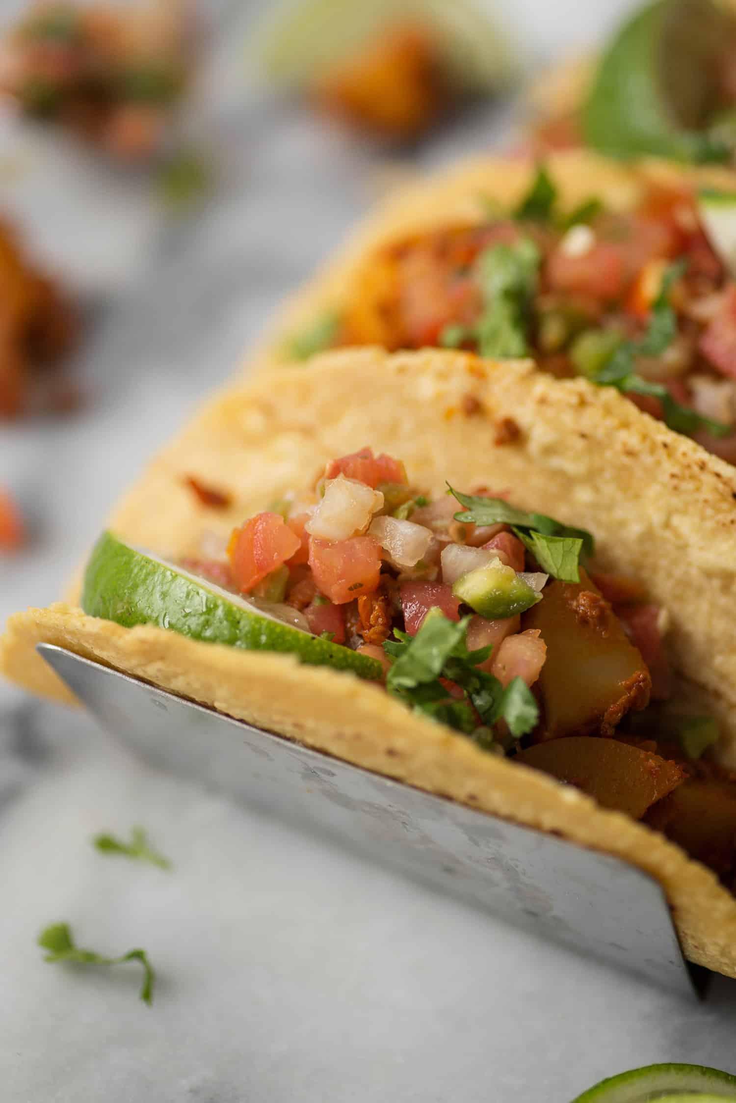 close up of vegan chorizo and potato taco with pico de gallo and lime