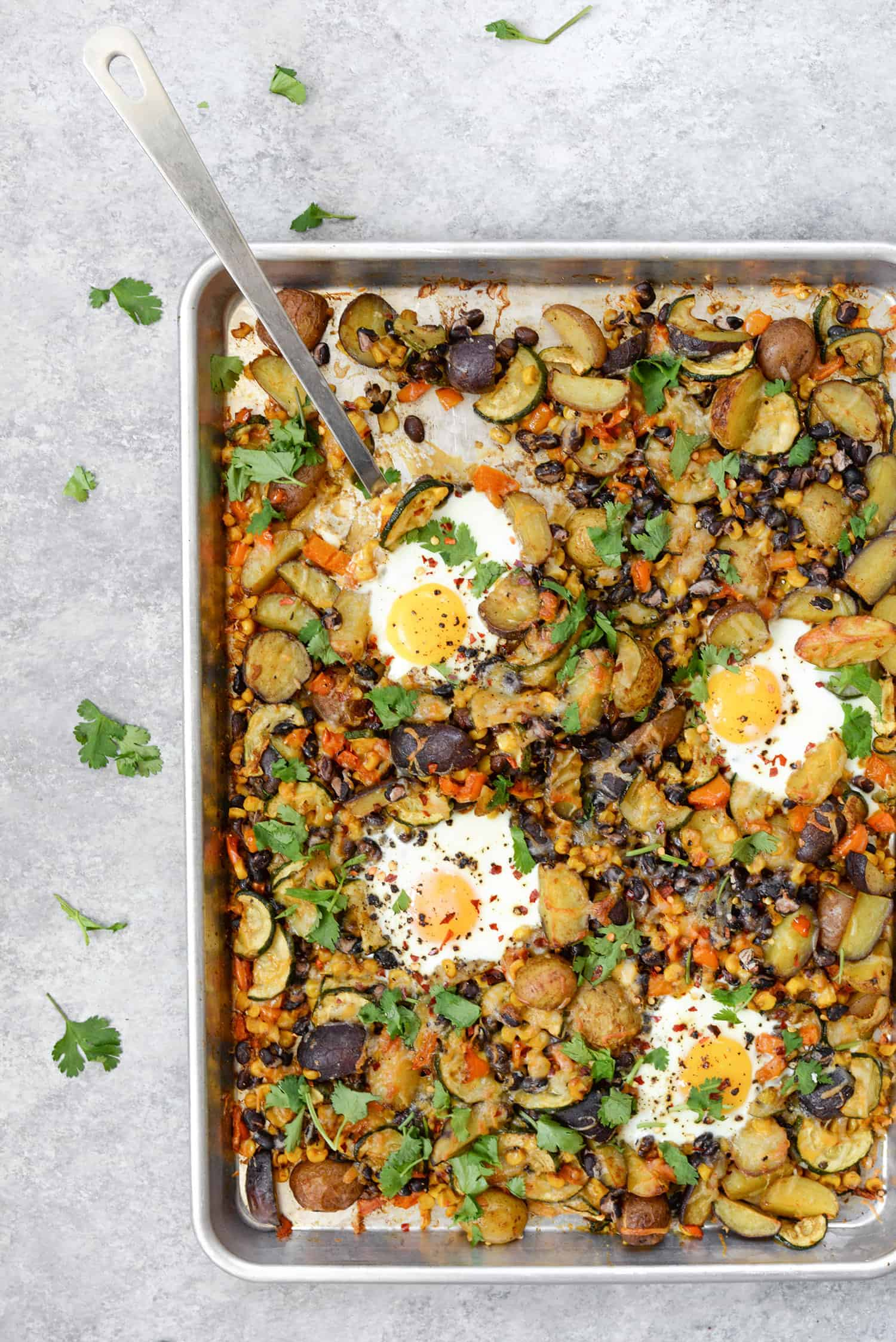 Sheet Pan Breakfast Hash! You are going to love this quick and easy dinner (or breakfast) idea. Roasted potatoes, zucchini, peppers, beans, corn and eggs. High-protein, vegetarian and gluten-free. | www.delishknowledge.com