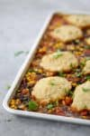 Sheet Pan Vegetable Chili with Beer Biscuits! You will love this all-in-one vegan sheet pan dinner. Roasted vegetable chili topped with whole wheat beer biscuits. | www.delishknowledge.com