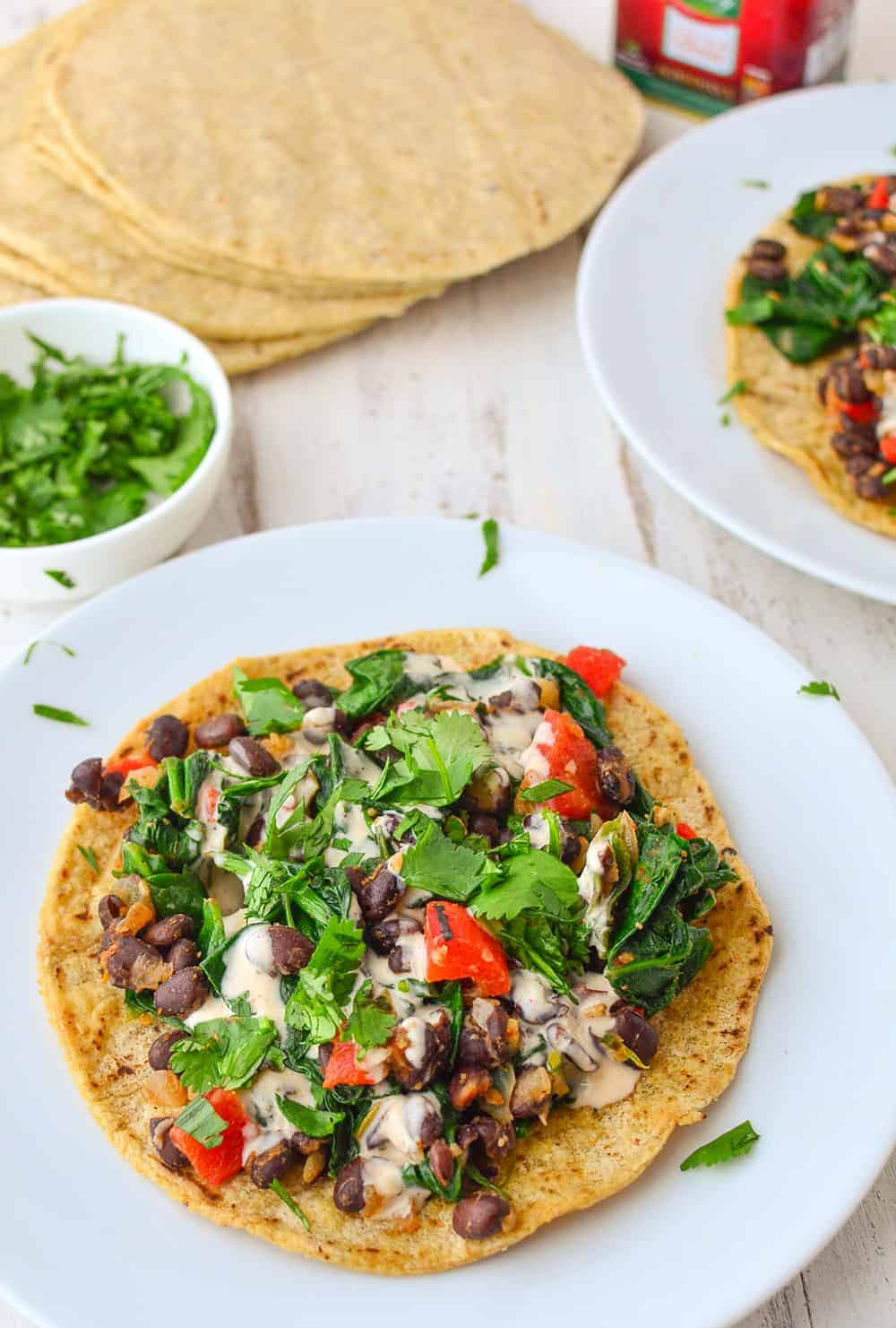 Smoky Black Bean Tostadas! Black bean and spinach filling topped with a smoky paprika sauce. Vegan and gluten-free.| www.delishknowledge.com
