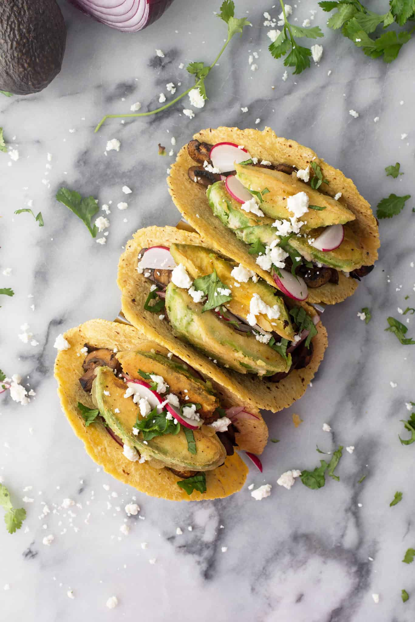 Spicy Mushroom and Black Bean Tacos with Crispy Avocado. These vegetarian tacos are loaded with flavor and texture! Crispy fried avocado, pickled onions, spicy mushroom and bean filling and goat cheese. | www.delishknowledge.com