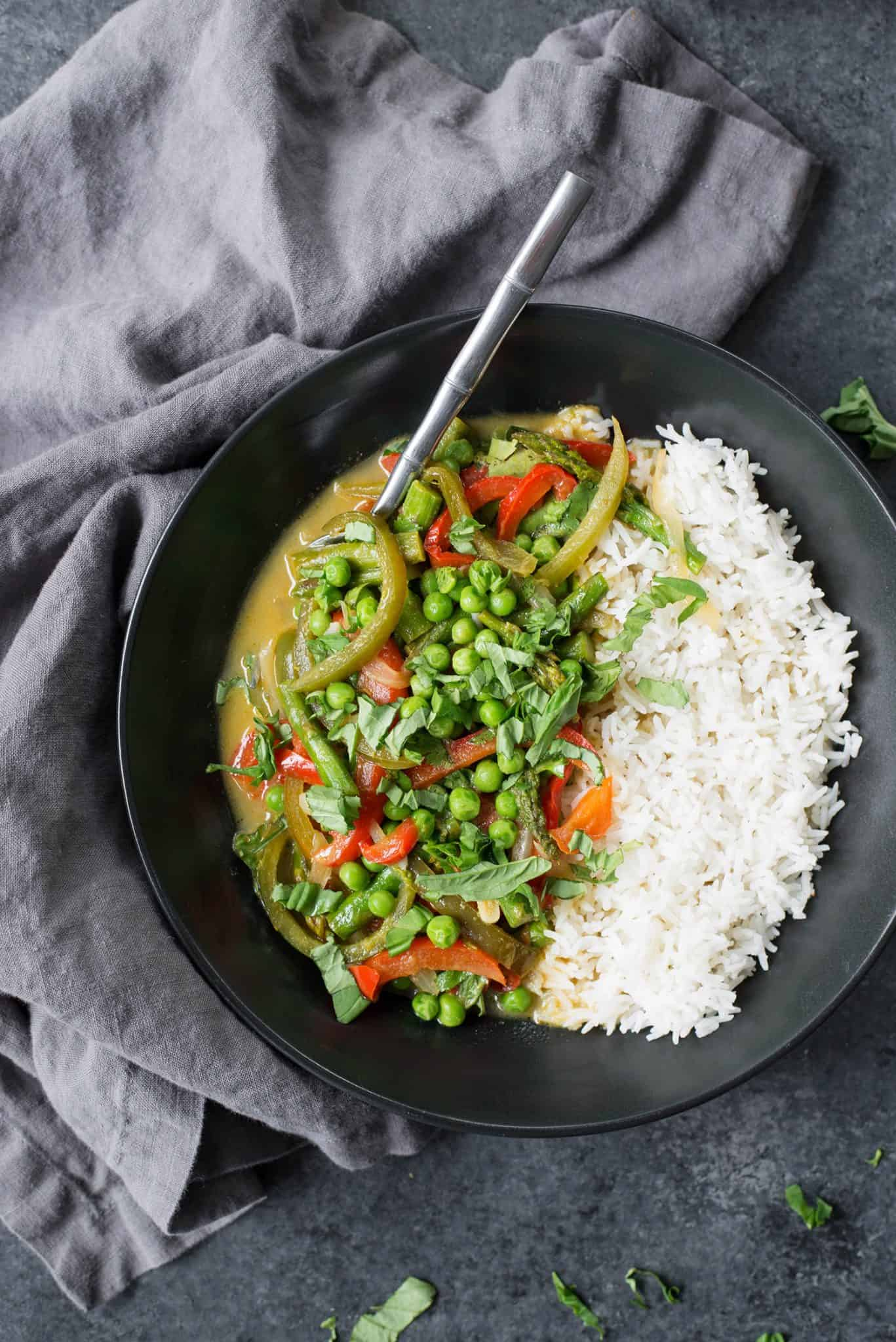 Spring Vegetable Thai Green Curry! This curry is packed with flavor and tons of vegetables. Quick green curry sauce with peppers, asparagus and peas. Vegan and Gluten-Free | www.delishknowledge.com