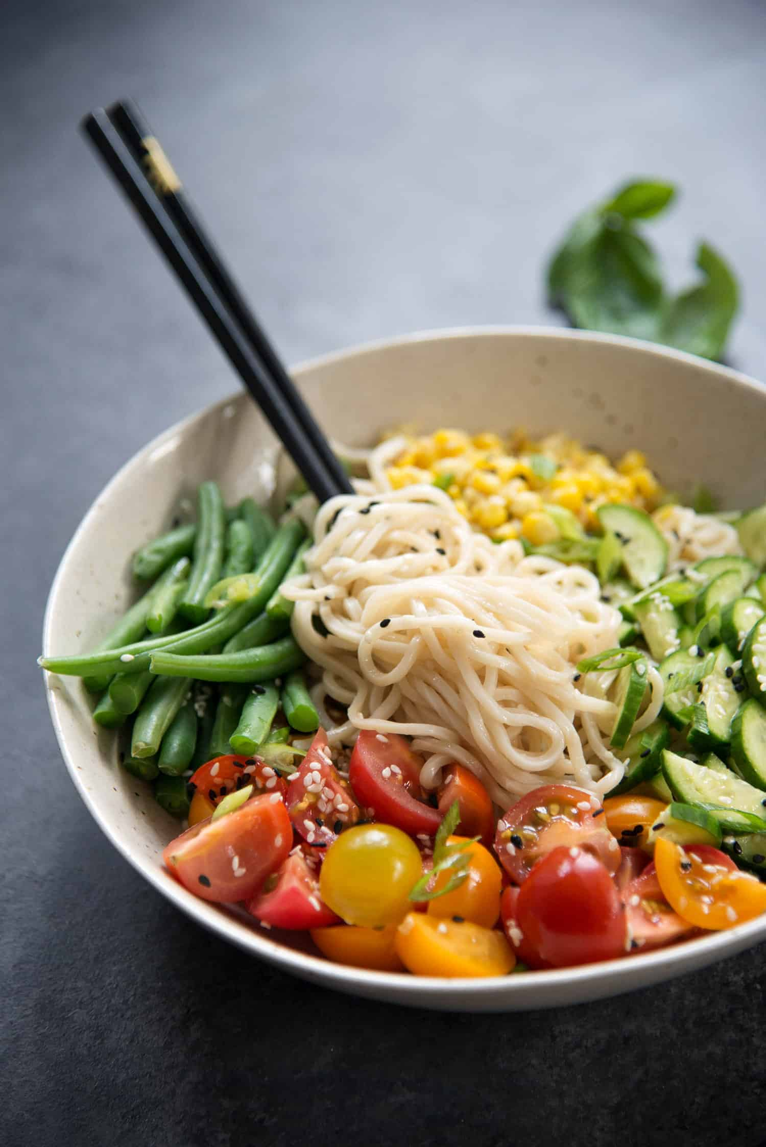 White bowl full of ramen noodles, fresh green beans, sliced tomatoes and other delicious fresh vegetables
