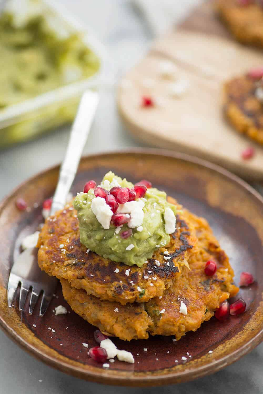 Sweet Potato Quinoa Cakes with Pomegranate Guacamole! A flavorful side dish for the holidays. Savory potato cakes with guacamole, feta and pomegranate.