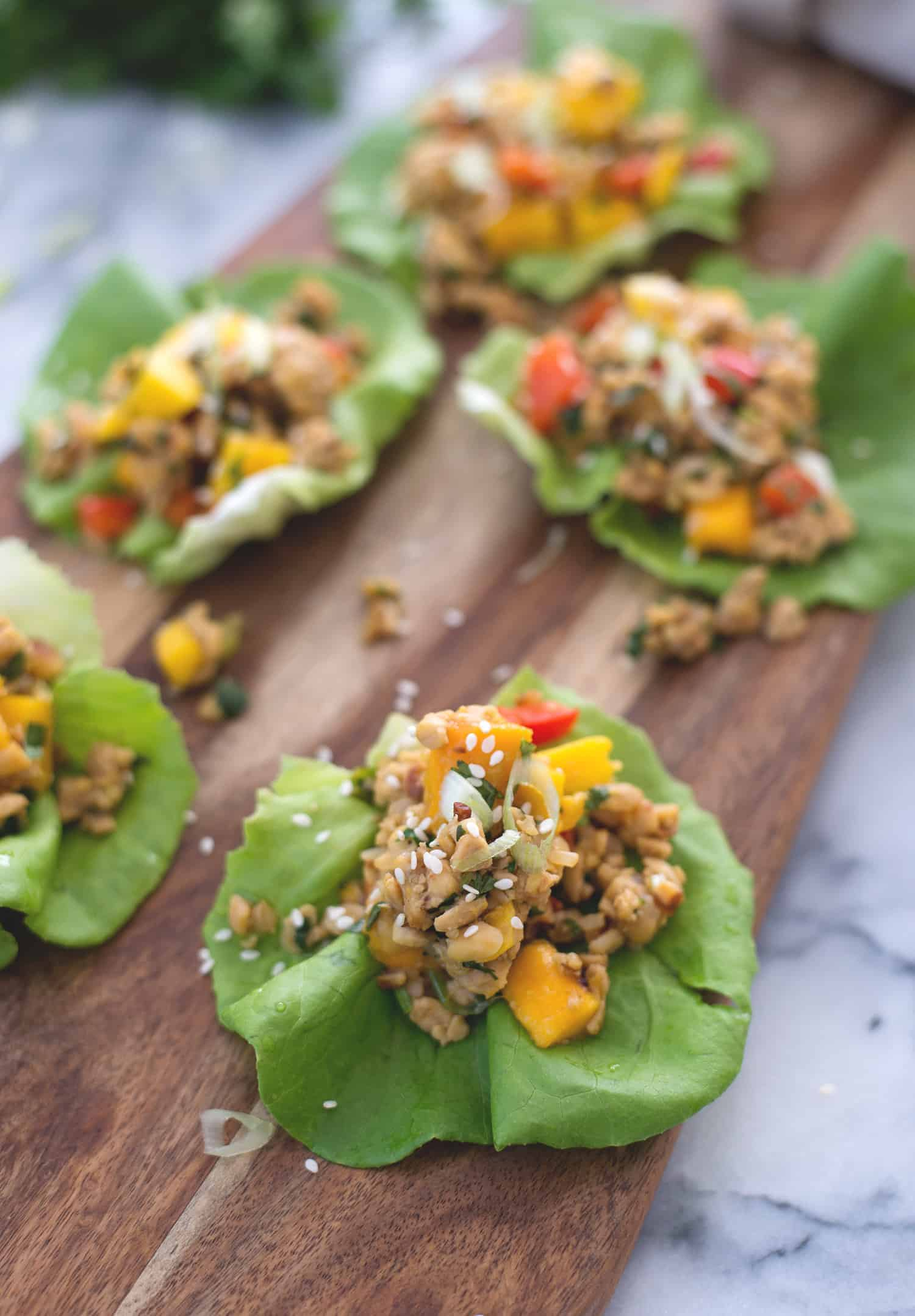 Tempeh Mango Lettuce Wraps! Spicy ground tempeh with peppers and mango, stuffed into butter lettuce cups. Vegan & Gluten-Free | www.delishknowledge.com