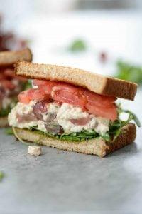 half sandwich of vegan tofu salad with grapes, tomato, arugula, celery