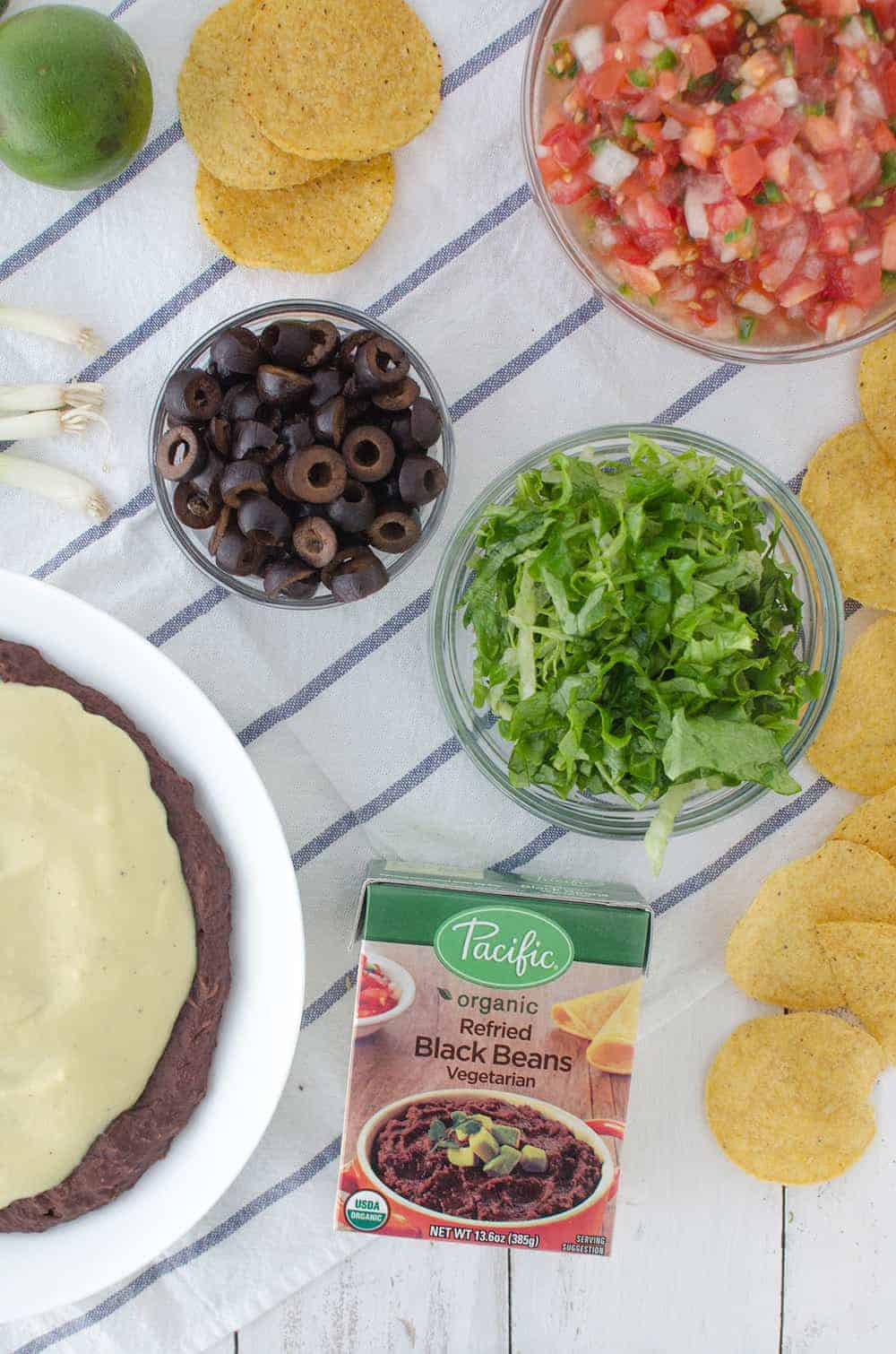 Vegan Mexican 7 Layer Dip! Refried black beans,quick vegan cheese sauce, guacamole, homemade pico de gallo, shredded lettuce, olives, and peppers! A must make for a healthy superbowl!   www.delishknowledge.com