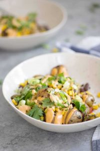 These nacho bowls are SO easy! Grilled potatoes covered with beans, corn, jalapenos and a creamy chipotle sauce. Vegan and Gluten-Free. | www.delishknowledge.com