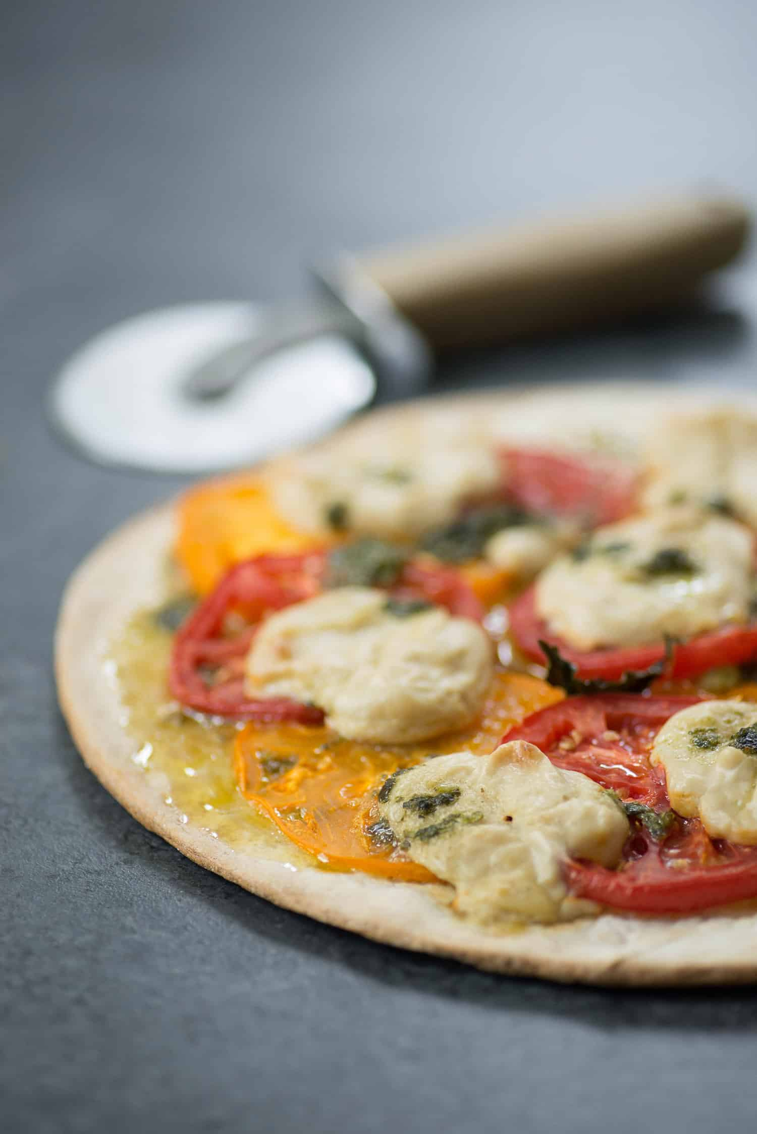 Vegan Pizza! Fresh margherita pizza with cashew mozzerella cheese, heirloom tomatoes and fresh basil. | www.delishknowledge.com