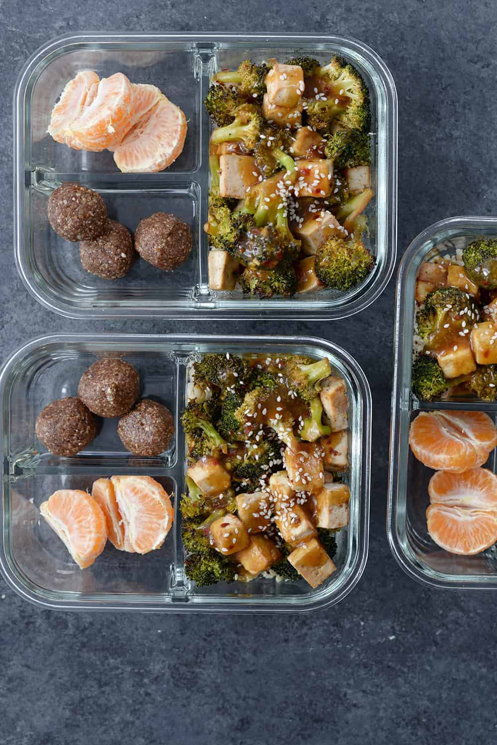 three meal prep containers with oranges, sheet pan tofu and nutella energy bites