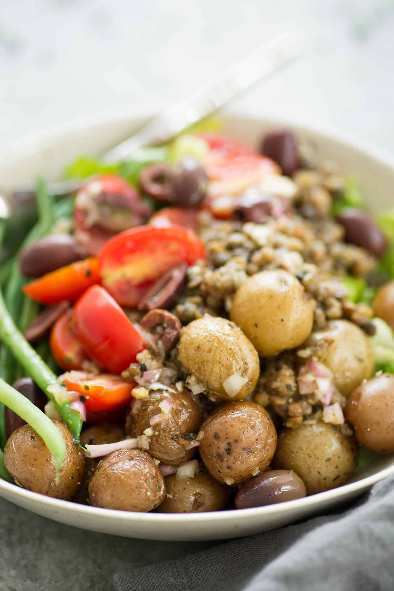 Lentil Nicoise Salad! You will love this protein packed plant-based meal. Potatoes, vegetables, seasoned lentils, green beans and a shallot dressing. Gluten-Free and Vegan | www.delishknowledge.com