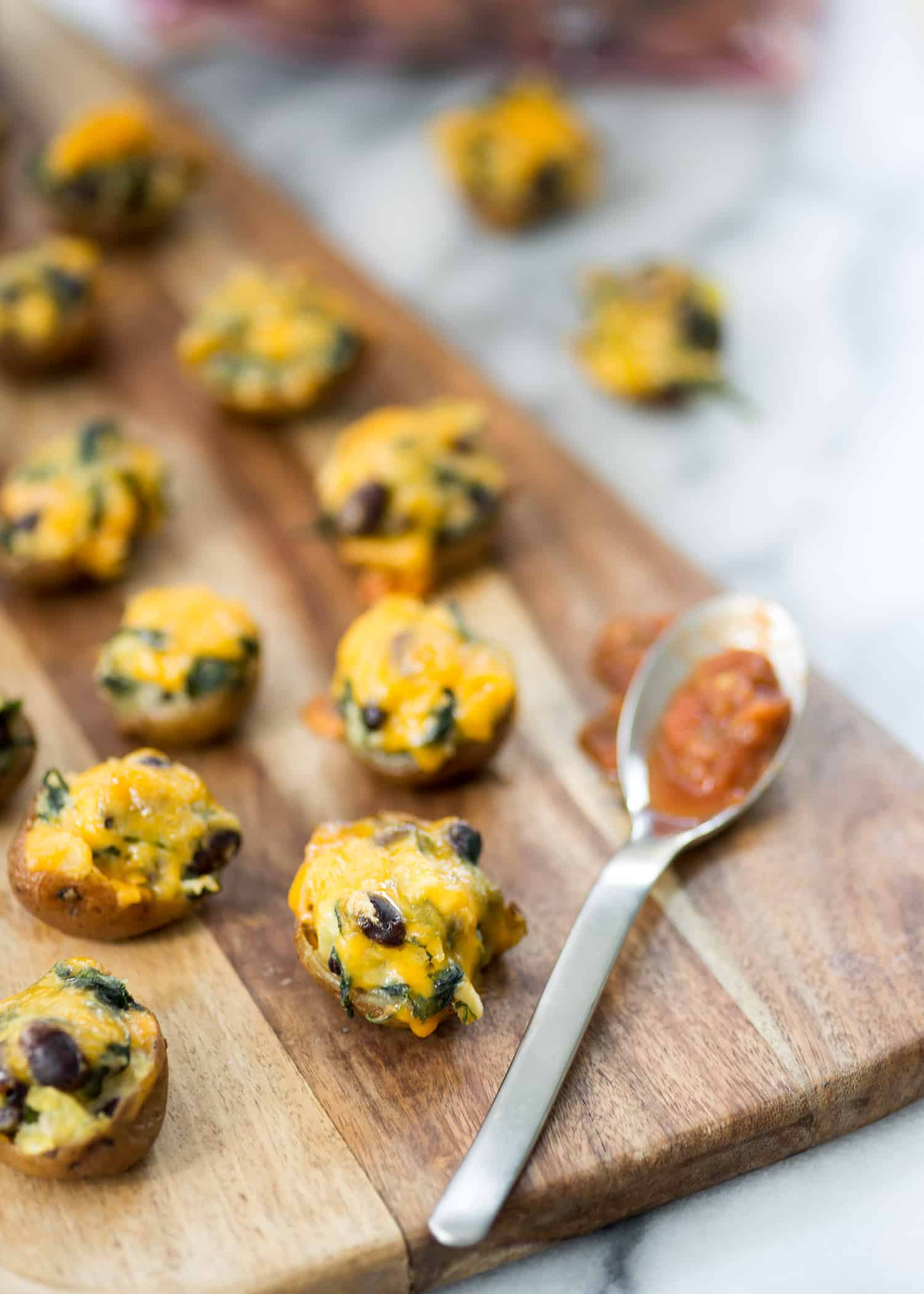 Vegetarian Southwestern Stuffed Potato Skins! Spicy potato, beans and spinach stuffed into potato skins and covered with mexican cheese. Vegetarian and Gluten-Free | www.delishknowledge.com