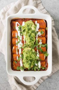 Vegan Fajita Enchiladas! These enchiladas are perfect for Cinco de Mayo. Roasted peppers, onions and beans covered in a homemade enchilada sauce and avocado. | www.delishknowledge.com