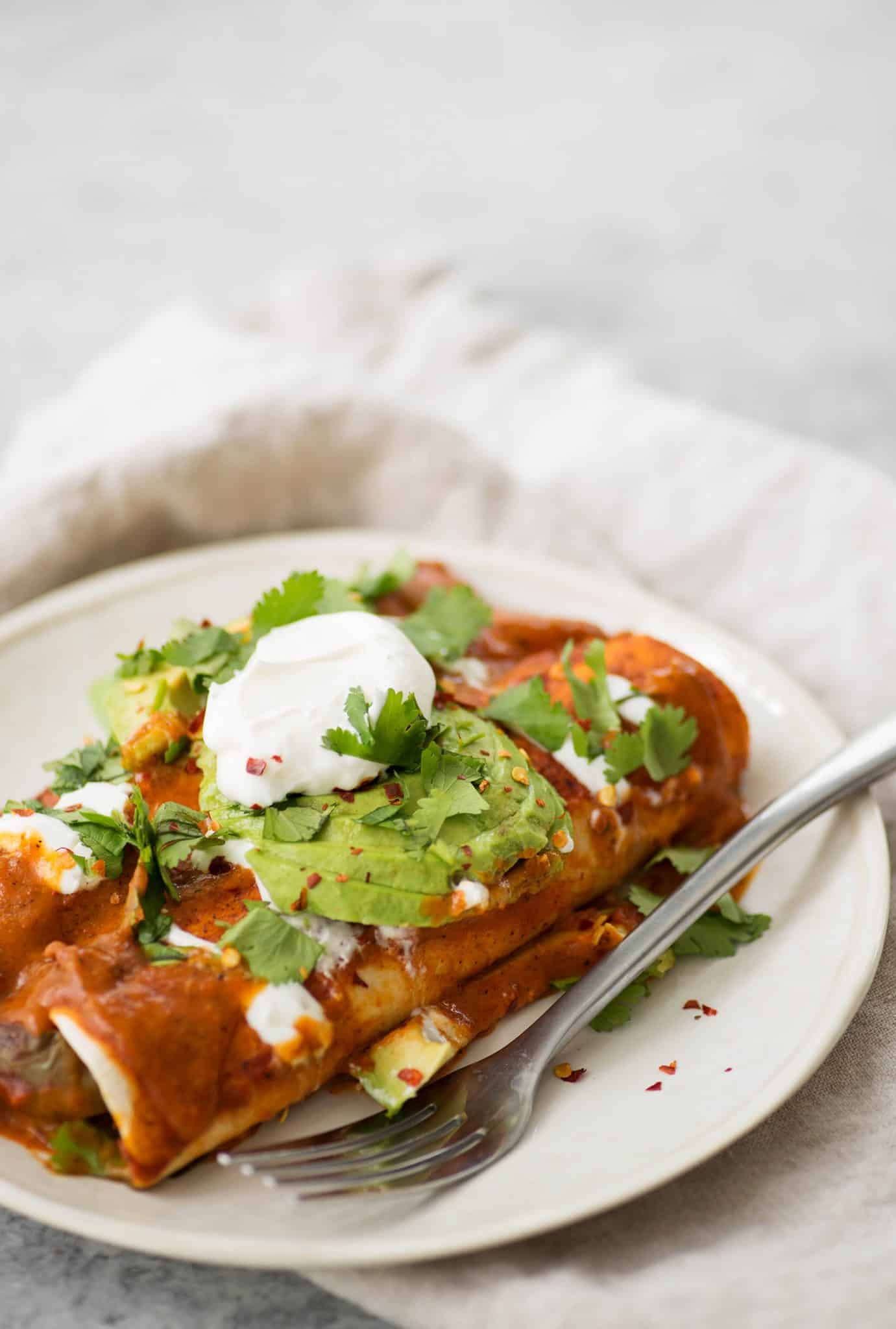 Vegan Fajita Enchiladas! These enchiladas are perfect for Cinco de Mayo. Roasted peppers, onions and beans covered in a homemade enchilada sauce and avocado.   www.delishknowledge.com