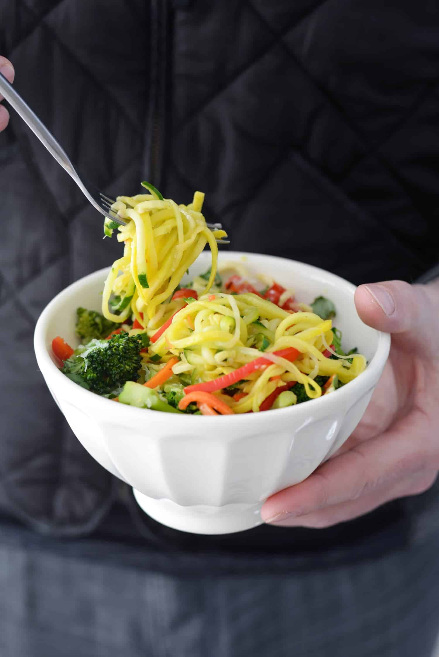 Fork curling and eating the zucchini noodle primavera