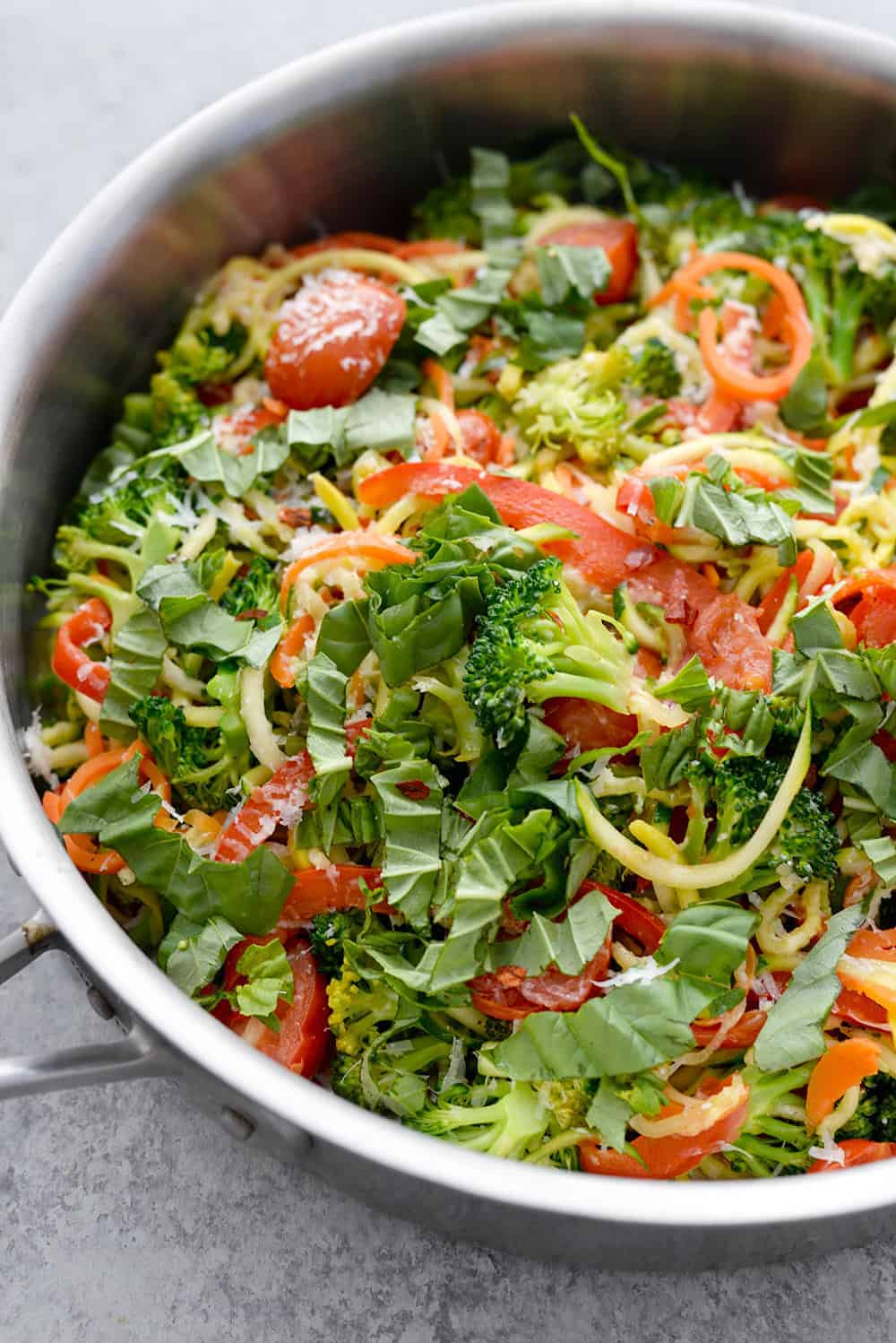 Skillet of zucchini zoodles with vegetables and herbs