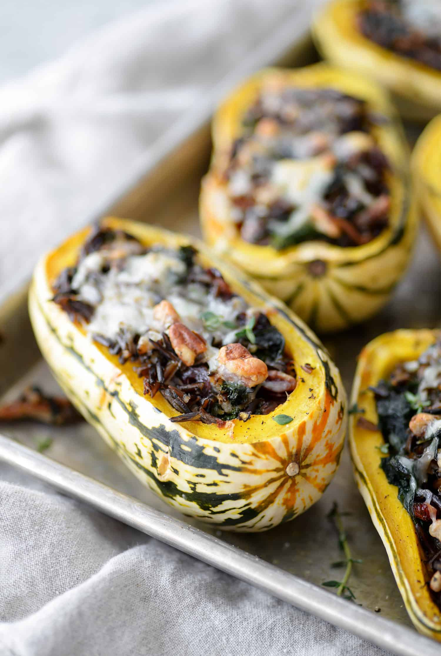 Wild Rice, Kale and Cranberry Stuffed Delicata Squash. The perfect vegetarian main dish. Roasted Squash stuffed with wild rice, kale, pecans, cranberries and topped with cheese. Gluten-free | www.delishknowledge.com