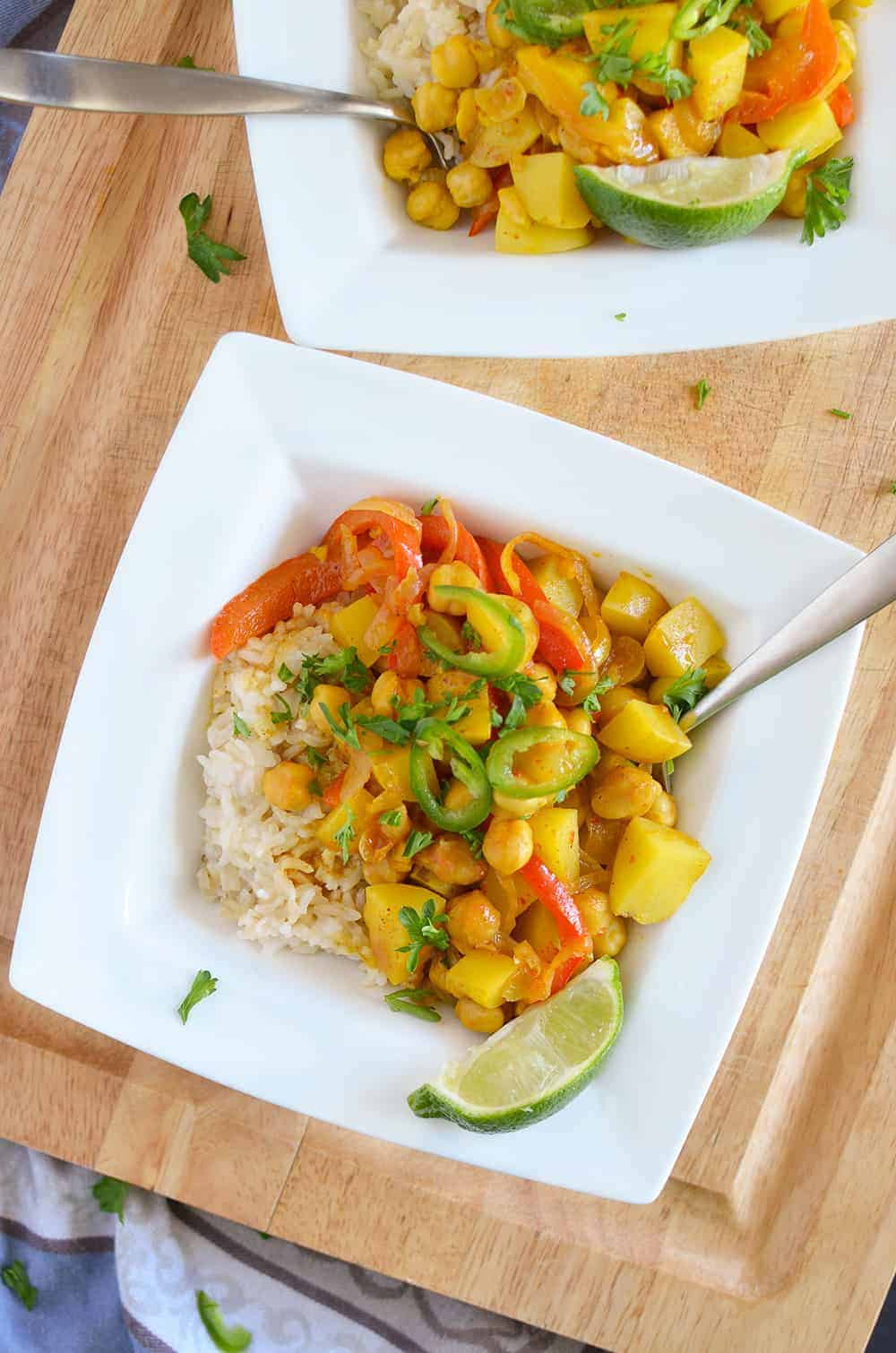Yellow Curry Bowls! These vegan and gluten free curry bowls are a MUST-MAKE! Potatoes, chickpeas & peppers simmered in a coconut curry sauce. | www.delishknowledge.com