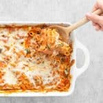 Serving the pasta bake with a wooden spoon
