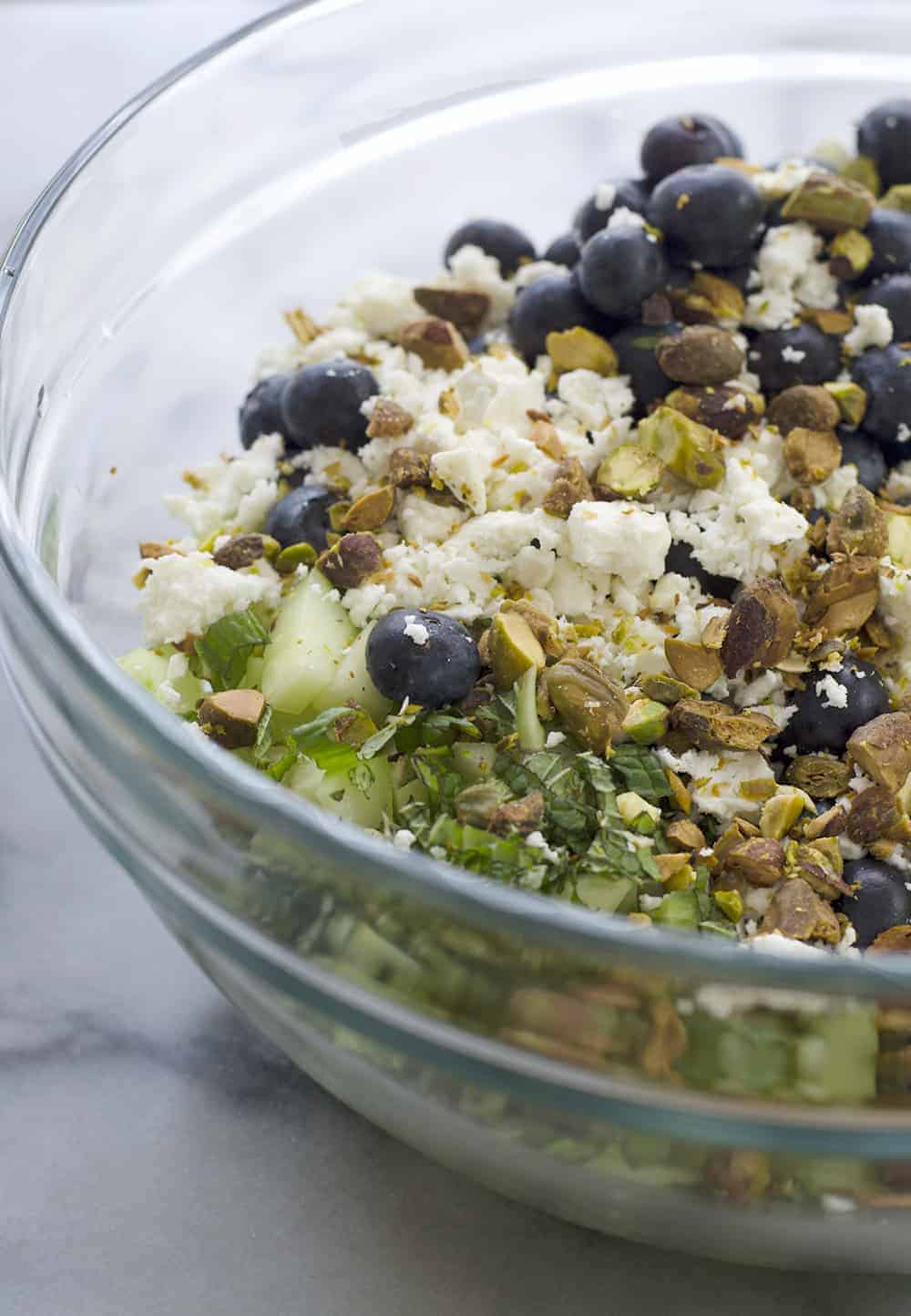 Blueberry Farro Salad! This sweet and salty salad is perfect for summer entertaining! Fresh blueberries, chewy farro, cucumber and feta in a lemon-mint dressing. Vegetarian | www.delishknowledge.com
