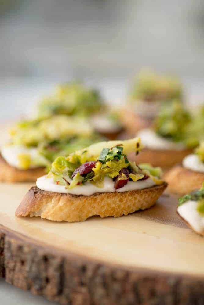 Vegan Brussels Sprout Crostini! Lemon-White Bean Spread topped with charred brussels sprouts and dried cranberry salad. A must-make for the holidays! | www.delishknowledge.com