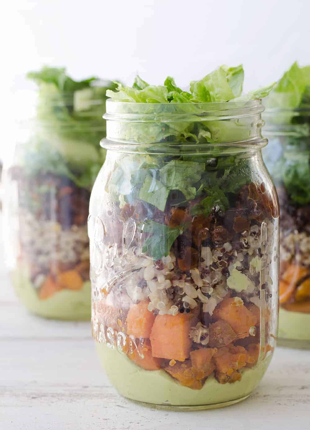 Burrito Bar Mason Jar Salads! Layers of avocado dressing, roasted sweet potato, quinoa, black bean and crispy lettuce. Vegan & Gluten-Free. | www.delishknowledge.com