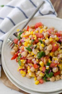 Corn, Tomato and Mint Salad! This gluten-free, vegan side dish is perfect for summer! Juicy tomatoes, fresh corn, onion, chickpeas and a lemon mint dressing. High-fiber and full of protein! | www.delishknowledge.com